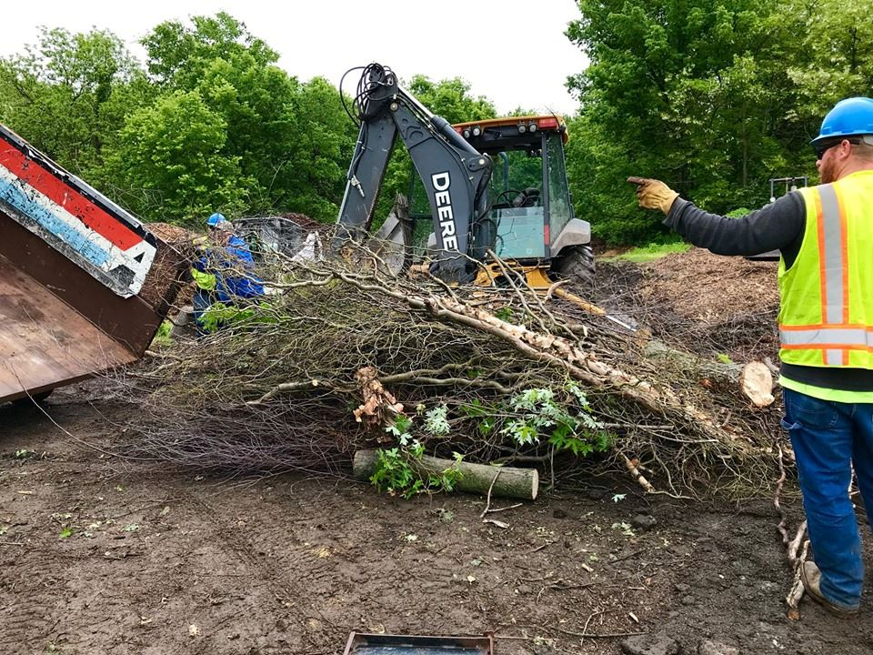 Brush is taken off a trailer before being put into a wood chipper at the 2019 Spring Brush Drop Off